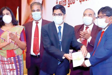 President - College of Community Dentistry Dr. P. L. P Jayashantha handing over the first publication of the book on oral health during COVID-19 to Former DG Health Services Dr. J. M. W. Jayasundarabandara.