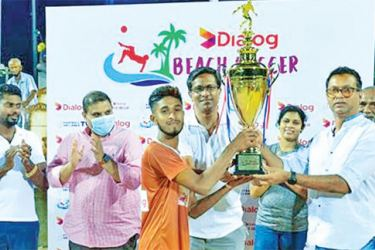 -Skipper of the Hambantota Hornets receiving the 'Dialog Beach Soccer Champions Trophy' from Manhara Wijeyawickrama, Senior General Manager - Channel Planning & Control of Dialog Axiata PLC. Also in picture (L-R) Nalin Hemakumara – Hambantota Football League President & Coordinating Secretary to Namal Rajapaksa, Dr. Manil Fernando – Chairman, Medical Committee, Anura de Silva – President, Football Federation of Sri Lanka, Shalika Ranaweera – Chairwoman, Women's Football and (partially covered) M M Ramees –