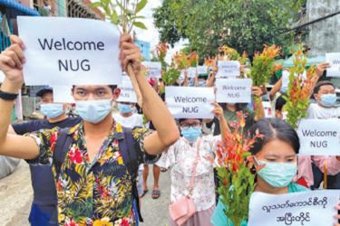 Anti-Government protesters hold placards to show their support and welcome the new National Unity Government (NUG) founded by ousted leader  Aung San Suu Kyi's National League for Democracy (NLD) legislators in Yangon, Myanmar on Saturday.