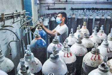 A worker refilling oxygen cylinders at India's Kanpur LLR Hospital, amid the rise in COVID-19 cases across the country.