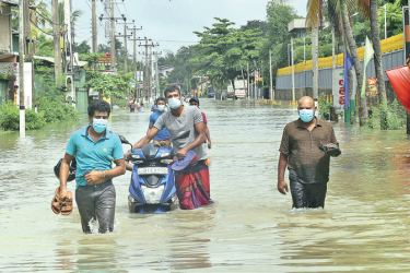 People wading through flood waters at Bandarawatte junction in Biyagama yesterday. Picture by Rukmal Gamage