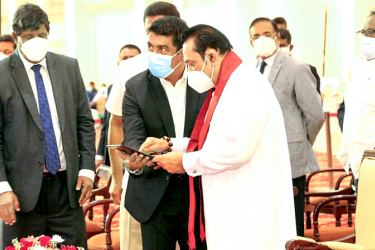 Prime Minister Mahinda Rajapaksa inaugurateed work on several flyovers and an elevated highway via new video technology from Temple Trees yesterday. Highways Minister Johnston Fernando is also in the picture. (Picture courtesy Highways Ministry Media Division)