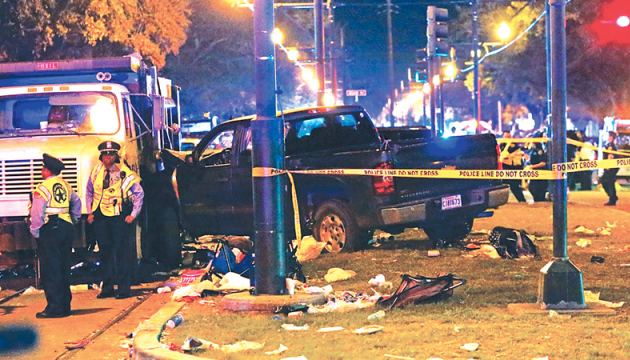Police stand next to a pickup truck that slammed into a crowd and other vehicles, causing multiple injuries, during the Krewe of Endymion parade in New Orleans on Saturday evening.