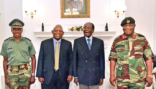 Zimbabwean President Robert Mugabe (Second Right) stands with Defence Forces Commander General Constantino Chiwenga (R) and South African envoys at the State House in Harare on Thursday.