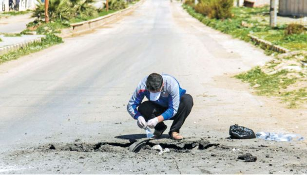 A Syrian man collects samples from the site of a suspected toxic gas attack.