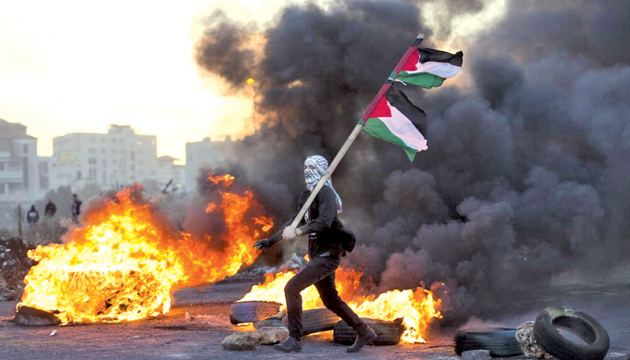 A Palestinian protester flies Palestinian flags during clashes with Israeli troops following protests against US President Donald Trump's decision to recognize Jerusalem as the capital of Israel, in the West Bank city of Ramallah on Saturday.