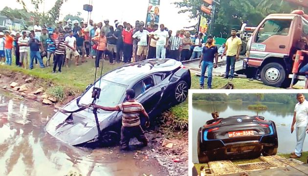 A BMW car, which was reportedly driven by a businessman, plunged into a canal at Thalawathugoda on Saturday morning after crashing into two other vehicles. Here, a recovery vehicle salvaging the car out.  Pictures by Duminda Senarath