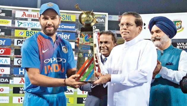 President Maithripala Sirisena presents the Hero Nidahas trophy to Indian captain Rohit Sharma at the end of the final at the R Premadasa Stadium yesterday. Pic by Rukmal Gamage