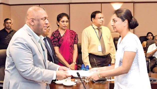 Minister Samaraweera presenting a letter of appointment to a newly selected Assistant Superintendent of Customs