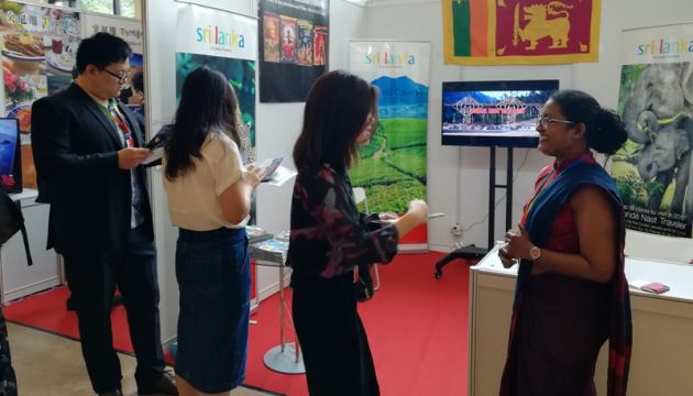Second Secretary of SL Embassy Inoka Weerasinghe in conversation with visitors to the booth.