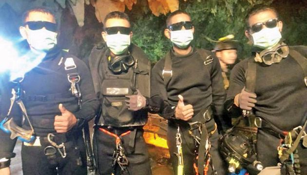 The last four Thai Navy SEALs giving a thumbs up after exiting safely from the Tham Luang cave following the rescue of the remaining four boys and their coach. - AFP