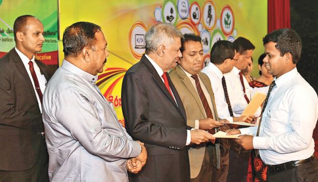 Prime Minister Ranil Wickremesinghe handing over an appointment letter to a teacher at the hand over ceremony held at Temple Trees yesterday. Education Minister Akila Viraj Kariyawasam, State Education Minister V. Radhakrishnan, Monitoring MP Imran Maharoof and officials look on.