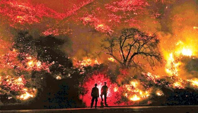Two men watch a wildfire burning out of control in southern California.