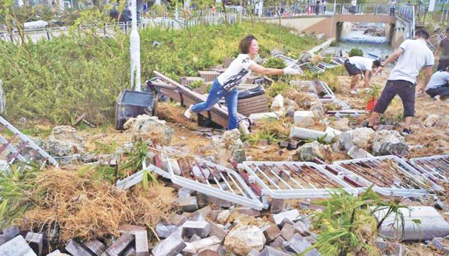 People clean-up debris caused by Typhoon Mangkhut outside a housing estate on the waterfront in Hong Kong on Monday.  - AFP