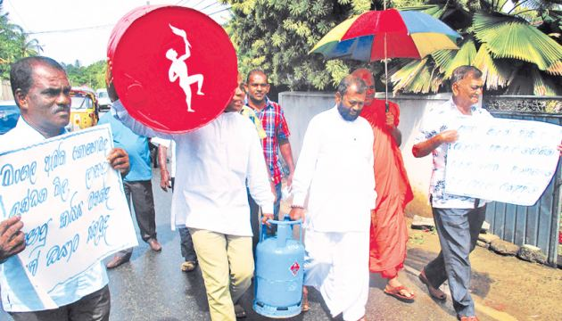 SP Councillors Shammu Ariyawansa and A.G.C. Piyasiri carry the fuel barrel and gas cylinder to protest the rising prices. Picture by Mahinda P. Liyanage - Galle Central Special Corr.