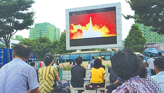 People watching as coverage of an ICBM missile test is displayed on a screen in a public square in Pyongyang.- AFP