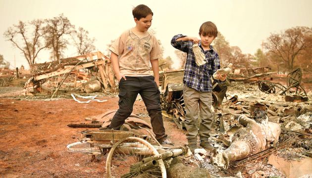 Jeremie (L) and and Jacob (R) Saylors look at religious statues they found in the burned remains of their home in Paradise, California on Sunday. - AFP