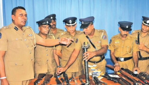 Police spokesman SP Ruwan Gunasekera and officers with the weapons cache.