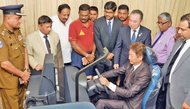 A Japanese official demonstrates the use of the simulator at the National Council for Road Safety, while Dr. Sisira Kodagoda and other officials look on.  Picture by Wimal Karunathileke