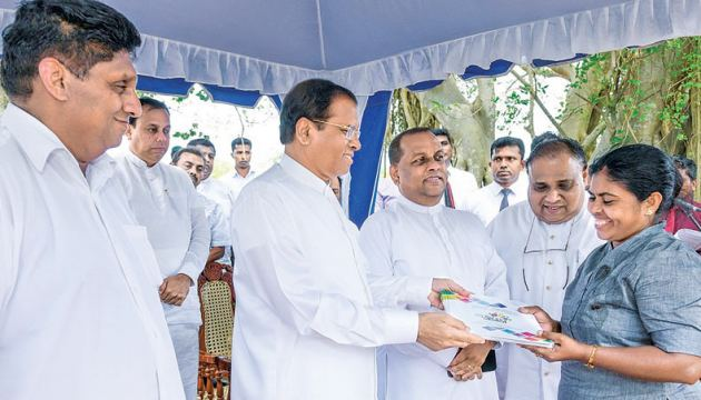 President Maithripala Sirisena presenting a cheque to a Grama Shakthi programme beneficiary.  Picture by President's Media Division