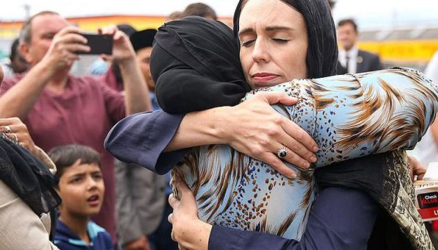 New Zealand's Prime Minister Jacinda Ardern,(R), hugs and consoles a woman as she visited Kilbirnie Mosque to lay flowers among tributes to Christchurch attack victims in Wellington.