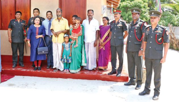 Jaffna Commander Major General Darshana Hettiarachchi, other high-ranking Army officers, and Mohan and Vadhani Shankar with one of the families who received a new house.