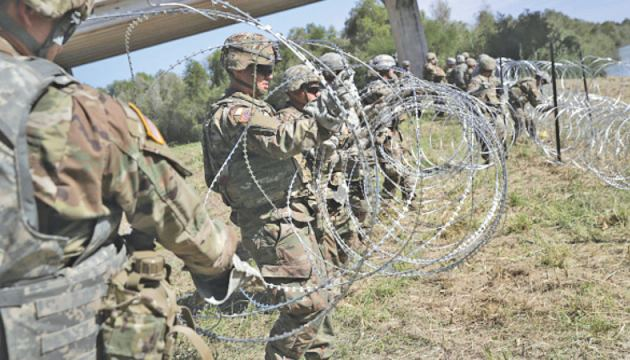 U.S. Marines help to build a concertina wire barricade at the U.S. Mexico border.