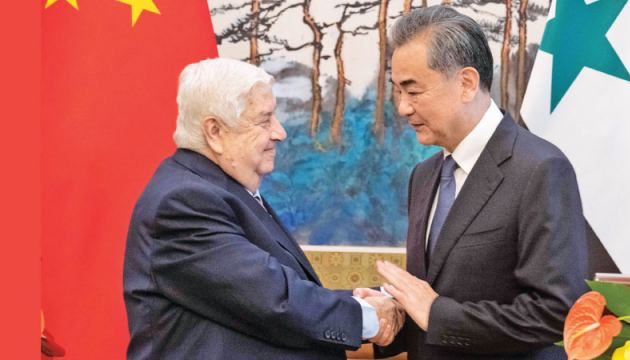 Syrian Foreign Minister Walid Muallem (L) shakes hands with Chinese Foreign Minister Wang Yi  after a press conference at Diaoyutai state guesthouse in Beijing yesterday.- AFP