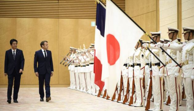 Japan's Prime Minister Shinzo Abe (L) walks with France's President Emmanuel Macron during an official ceremony at the prime minister's official residence in Tokyo on June 26, 2019.