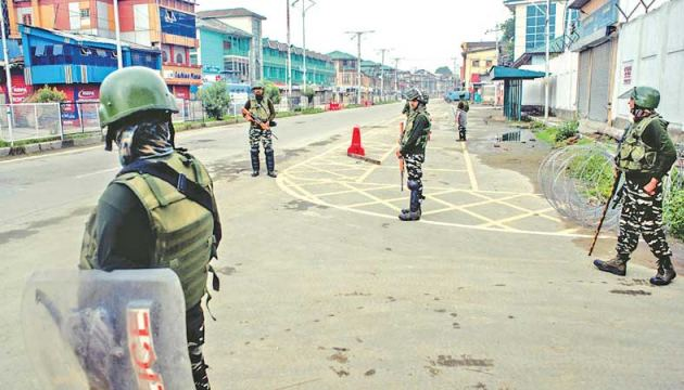 Indian government forces stand guard in the deserted city centre of Srinagar on August 15.
