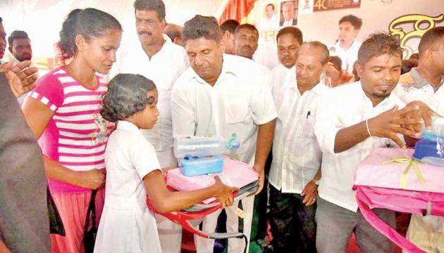 Minister Sajith Premadasa distributes school bags and other items to students, at the opening of a model village.