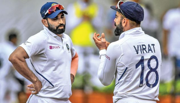 India's Mohammed Shami (L) looks on as captain Virat Kohli applauds during the third day of the first Test cricket match of a two-match series against Bangladesh at Holkar Cricket Stadium in Indore on Saturday. - AFP