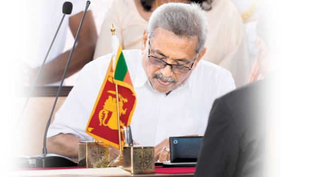 President Gotabaya Rajapaksa signs documents during his swearing-in ceremony. - AFP