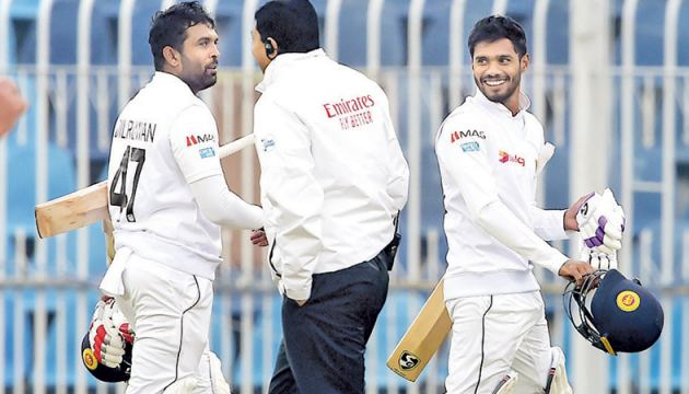 Sri Lanka's Dhananjaya de Silva (R) and Dilruwan Perera (L) walk back to the pavilion after the game was stopped due to bad light during the third day of the first Test cricket against Pakistan in Rawalpindi on Friday. - AFP
