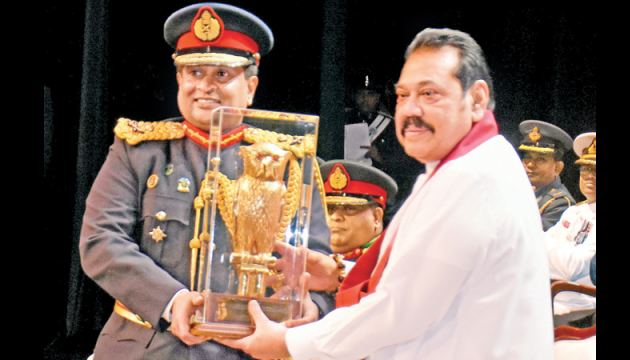 Prime Minister Mahinda Rajapaksa receives a memento from the Commandant of the Defence Services Command and Staff College Major General Prabath Dematanptiya at the graduation ceremony held at the Nelum Pokuna Theatre on Friday. Picture by Gayan Pushpika