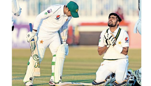 Pakistan's Babar Azam (R) celebrates after scoring century as teammate Pakistan's Abid Ali looks on during the fifth and final day of the first Test cricket match against Sri Lanka at the Rawalpindi Cricket Stadium in Rawalpindi on Sunday. AFP