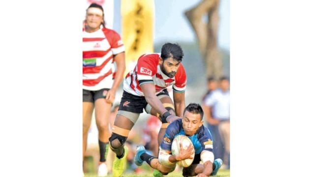 Air Force Sports Club fly half Gayan Iddamalgoda scoring a try with two CH and FC defenders making a vain attempt to foil him in their Dialog 'A' division league rugby match played at Ratmalana yesterday which Air Force won 39-22. Picture by Samantha Weerasiri
