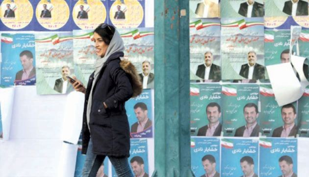 An Iranian woman walks past electoral posters in a street of the capital Tehran on Tuesday ahead of this week's Parliamentary elections. -  AFP