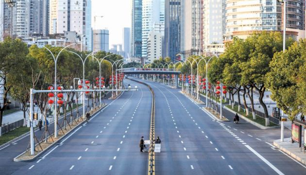 This photo taken on Thursday shows two staff members crossing an empty road as they deliver vegetables to a hospital in Wuhan in China's Hubei province. - AFP