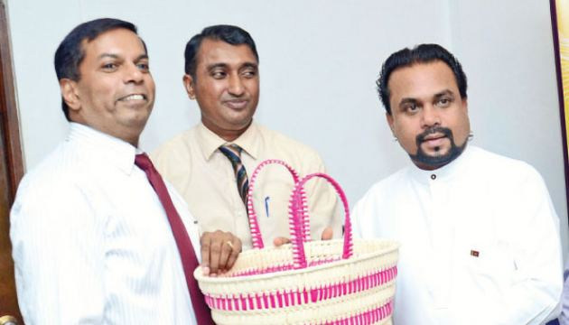 Minister Weerawansa is planning to market Palmyrah products, made in North at CWE outlets giving an additional income to producers. Here Chairman Palmyrah Development Board Krishantha Pathiraja is presenting some products to Minister Weerawansa looked on by Chairman, CWE, Nushad Perera. Picture by Wimal Karunatillike