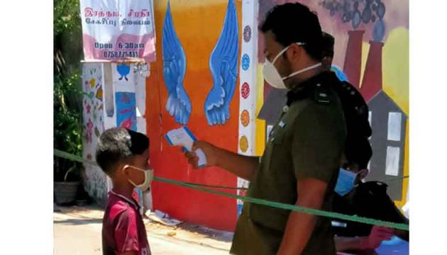 Public Health Inspectors check the temperature  of a child in  Orugodawatte, Colombo  (Picture by Hirantha Gunathilaka)