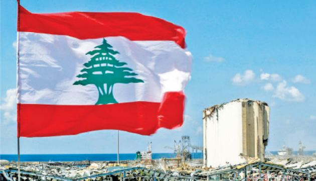 A Lebanese flag flying along a bridge near the port of Lebanon's capital Beirut, with the damaged grain silos seen in the background. - AFP