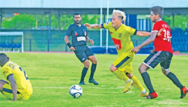 Colombo Football Club(CFC) striker Zarwan Johar advances with the ball is challenged by Sarith Chamika of SLTB SC in their Vantage FFSL President's Cup soccer encounter played at Sugathadasa Stadium yesterday.