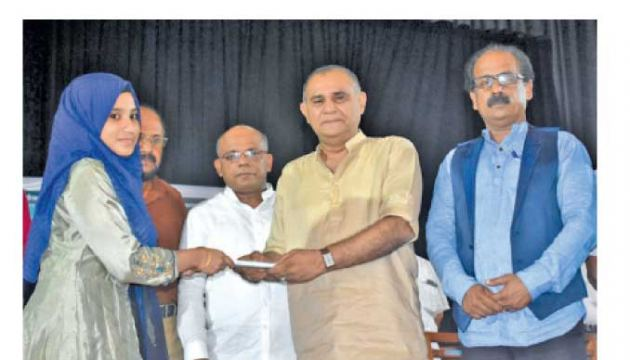 National Congress Leader and Member of Parliament A.L.M.Athaullah receiving the first copy of the book. Author A.S.Ahamed Kiyas was also present. (Picture by M.A.Phakurdeen – Addalaicheni Group Correspondent)