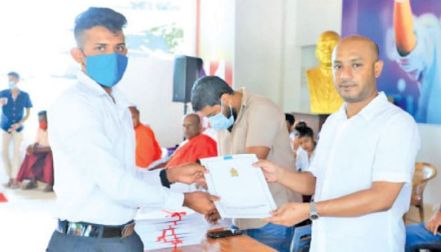A youth receiving his appointment letter from State Minister Duminda Dissanayake.