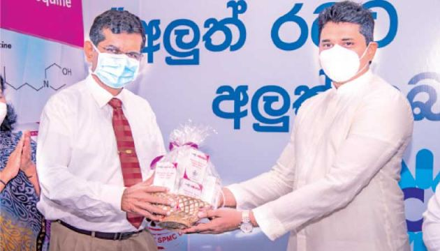 "State Minister of Production, Supply and Regulation of Pharmaceuticals Prof. Channa Jayasumana presenting the third drug produced locally under the ""New Drugs for a New Country"" programme to Consultant Dr.Ananda Wijewickrema."