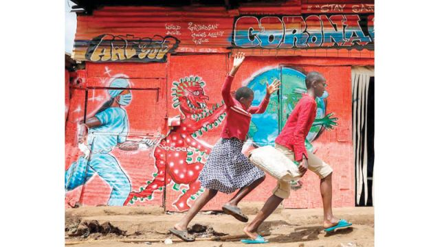 Children run past al mural warning people about the dangers of the COVID-19 pandemic in the Kibera settlement in Nairobi, Kenya.