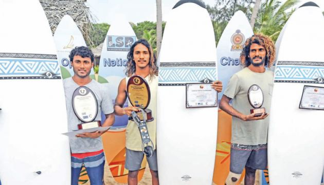 The three surfers who brought honor for Sri Lanka at the Surfing Championship held at Arugambay Beach, yesterday. (From left) Aasnka Sanjeeva (Arugam Bay SC), Lakshitha Madushan (Weligama SC) and lasitha Prabath pose with their awards.                      Picture by Sulochana Gamage