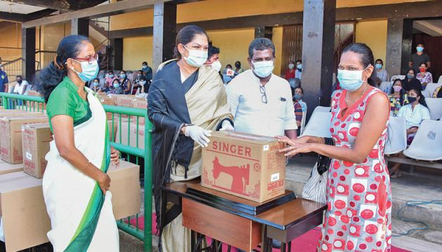 A woman receiving a sewing machine from Colombo Mayor Rosy Senanayake.