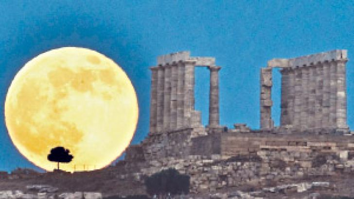 A supermoon rises next to the ancient Greek temple of Poseidon at Cape Sounion, around 65 kilometres south of Athens.AFP